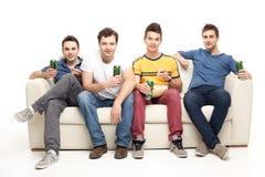 Jeunes hommes buvant de la bière mangeant du maïs éclaté Photos stock
