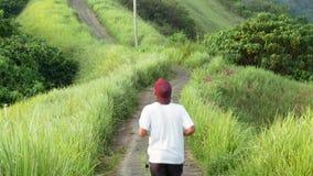 Jeunes hommes courant au-dessus de la colline verte au-dessus du fond de forêt de jungle traînée des artistes clips vidéos