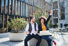 Jeunes hommes d'affaires avec l'ordinateur portable dehors dans la cour, exprimant l'excitation photo libre de droits