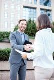 Jeunes hommes d'affaires féminins et masculins se serrant la main après une réunion réussie devant un immeuble de bureaux photo stock