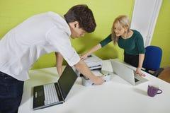 Jeunes hommes d'affaires installant l'imprimante avec des ordinateurs portables au bureau Photographie stock