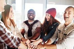 Jeunes hommes d'affaires joignant des mains ensemble Photo stock