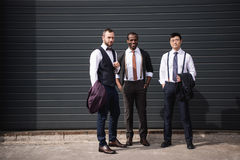 Jeunes hommes d'affaires multi-ethniques élégants dans le formalwear se tenant dehors Photographie stock