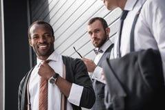 Jeunes hommes d'affaires multi-ethniques élégants dans le formalwear se tenant dehors Images stock