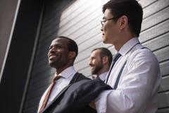 Jeunes hommes d'affaires multi-ethniques élégants dans le formalwear se tenant dehors Images libres de droits