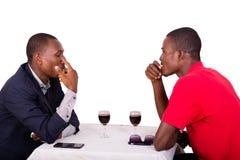 Jeunes hommes d'affaires parlant des affaires tout en buvant du vin à la table image libre de droits