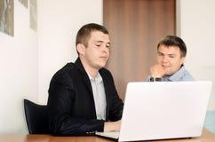 Jeunes hommes d'affaires regardant l'ordinateur portable sur le Tableau Photos stock