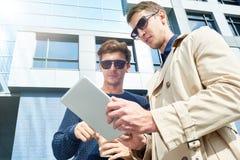 Jeunes hommes d'affaires utilisant la Tablette dehors Photo stock