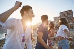 Jeunes hommes dansant avec leurs amies sur la plage Photo libre de droits