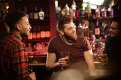Jeunes hommes de sourire buvant de la bière Images libres de droits
