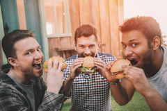 Jeunes hommes de sourire mangeant les hamburgers frais et regarder l'appareil-photo Photo stock