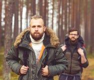 Jeunes hommes de touristes avec des sacs à dos dans la forêt Image stock