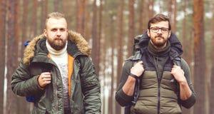 Jeunes hommes de touristes avec des sacs à dos dans la forêt Image libre de droits