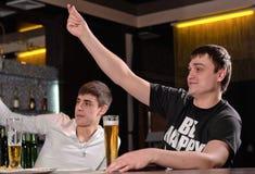 Jeunes hommes demandant l'attention dans le bar Photos libres de droits