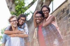 Jeunes hommes donnant sur le dos aux femmes Image libre de droits