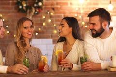 Jeunes hommes et femmes buvant le cocktail à la partie Image libre de droits