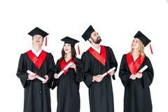 Jeunes hommes et femmes dans des robes d'obtention du diplôme et taloches tenant des diplômes Photos libres de droits