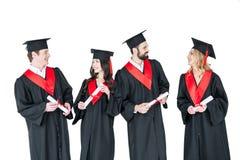 Jeunes hommes et femmes dans des robes d'obtention du diplôme et taloches tenant des diplômes Images stock