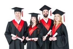Jeunes hommes et femmes dans des robes d'obtention du diplôme et taloches tenant des diplômes Photos stock