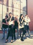 Jeunes hommes et femmes de mode invitant des téléphones portables Image libre de droits
