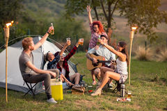 Jeunes hommes et femmes grillant avec de la bière sur le coucher du soleil en nature Photo stock
