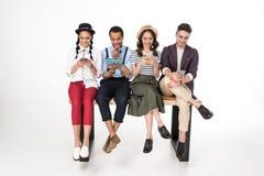 Jeunes hommes et femmes s'asseyant ensemble sur le banc et à l'aide des dispositifs numériques Photographie stock
