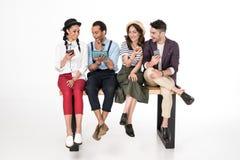 Jeunes hommes et femmes s'asseyant ensemble sur le banc et à l'aide des dispositifs numériques Images stock