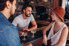 Jeunes hommes et femmes se réunissant dans un café et une discussion Photo stock