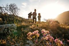 Jeunes hommes et femmes trimardant dans la campagne Photographie stock libre de droits