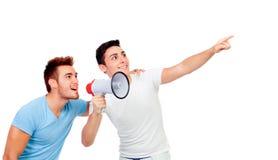 Jeunes hommes et ses cris perçants d'ami par un mégaphone Images stock
