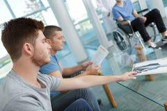 Jeunes hommes et un dans le fauteuil roulant dans la salle d'attente Images stock