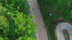 Jeunes hommes faisant de la planche à roulettes en parc moderne vert sur la route spéciale banque de vidéos