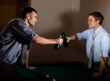 Jeunes hommes faisant tinter des bouteilles à bière au billard Images stock