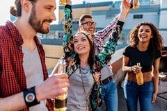 Jeunes hommes gais et femmes buvant de la bière sur le toit Images stock