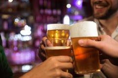Jeunes hommes grillant avec de la bière tout en se reposant dans le bar ensemble Photos stock