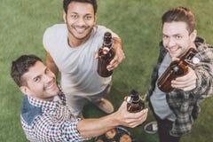Jeunes hommes heureux buvant de la bière et faisant le barbecue Photo stock