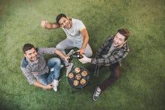 Jeunes hommes heureux buvant de la bière et s'asseyant sur l'herbe tout en grillant la viande Photo libre de droits