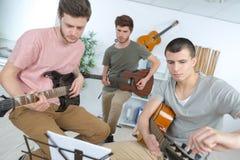 Jeunes hommes heureux jouant la guitare avec des amis à la maison Photos stock