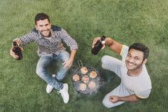 Jeunes hommes heureux s'asseyant sur l'herbe avec des bouteilles à bière et faisant le barbecue Photo libre de droits