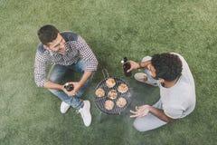 Jeunes hommes heureux s'asseyant sur l'herbe avec des bouteilles à bière et faisant le barbecue Image stock