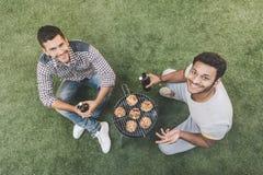Jeunes hommes heureux s'asseyant sur l'herbe avec des bouteilles à bière et grillant la viande Photos libres de droits