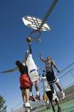Jeunes hommes jouant le basket-ball sur la cour Images stock