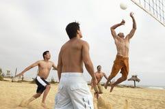 Jeunes hommes jouant le volleyball sur la plage Image stock