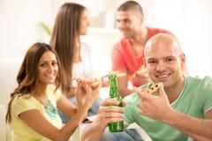 Jeunes hommes mangeant de la pizza Image stock