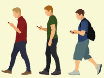 Jeunes hommes marchant et textotant Photo stock
