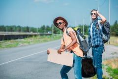 jeunes hommes multi-ethniques avec le carton vide recherchant la voiture tout en faisant de l'auto-stop Photo libre de droits