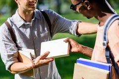Jeunes hommes multi-ethniques tenant des livres tout en se tenant en parc Images stock
