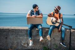 jeunes hommes multiculturels avec le carton et la guitare se reposant sur le parapet tout en faisant de l'auto-stop Photo libre de droits