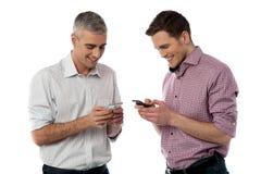 Jeunes hommes occasionnels à l'aide de leur téléphone intelligent Photographie stock