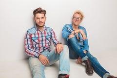 Jeunes hommes occasionnels heureux s'asseyant sur le plancher Images libres de droits